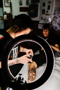 Unrecognizable man tattooer using smartphone to take picture of tattoo on leg of crop customer for portfolio in contemporary studio