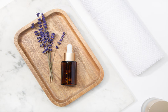 Top view lavender flower and its essential oil on a bottle drop at a marble table on wooden tray