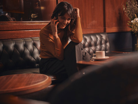 Stylish cheerful woman talking on mobile phone comfortably sitting at round table in cafe