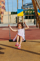 Full length little girl sitting on swing and looking away while resting on playground on sunny summer day