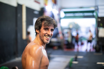 Cheerful athlete standing in gym