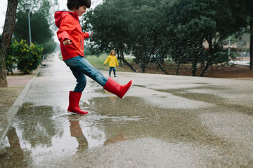 Adorable joyful children in red and yellow raincoat and rubber boots having fun playing in puddle in street in park in gray day