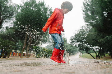 Adorable joyful child in red raincoat and rubber boots having fun jumping in puddle on street in park in gray day
