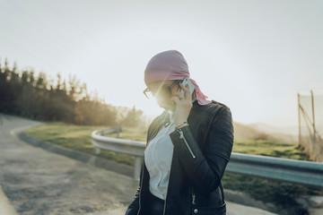 Stylish woman walking on road and talking smartphone