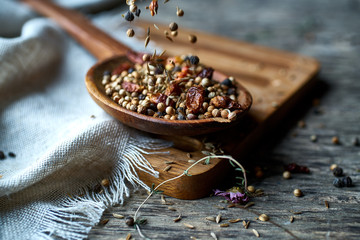 Dry mix of spices and dried berries in spoon on table