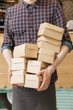 Unrecognizable man in plaid shirt holding lots of small cardboard boxes with delivered food in restaurant