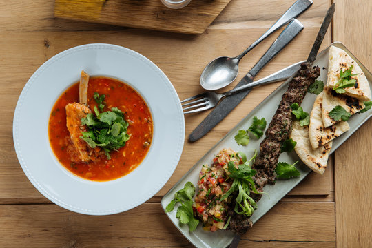 Top view of red soup with meat and fresh herbs on wooden table with kebab and flat bread in restaurant