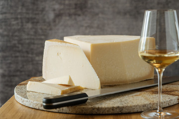 Gourmet appetizing block of cheese knife on cutting board and wine in glass on table