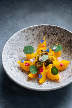 From above of sliced of orange fruit leading out in circle with fried white mushrooms in center on stylish plate