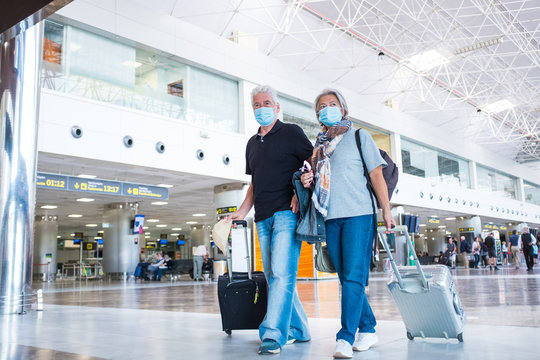 couple of two seniors or mature people walking in the airport going to their gate and take their flight wearing medical mask to prevent virus like coronavirus or covid-19 - carrying luggage or trolley