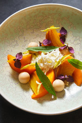 Close up of mango salad served with herbs on plate