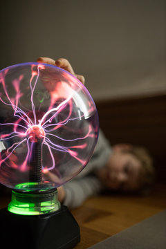 Boy looking at mysterious glass lightening lamp on table