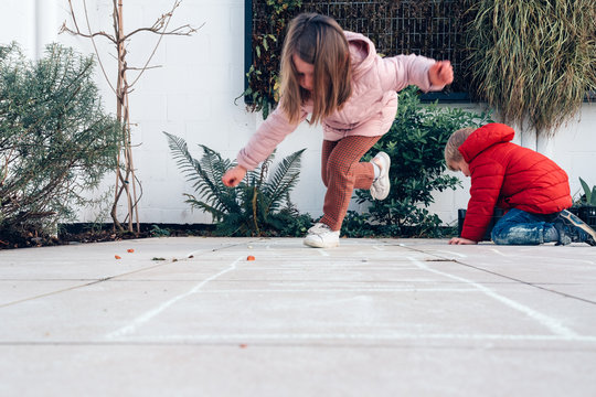 children playing hopscotch in a terrace outdoors