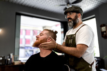 Side view of barber doing face massage to handsome redhead man with sitting in chair