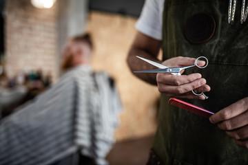 Unrecognizable crop man hairdresser holding scissors and comb in modern barbershop