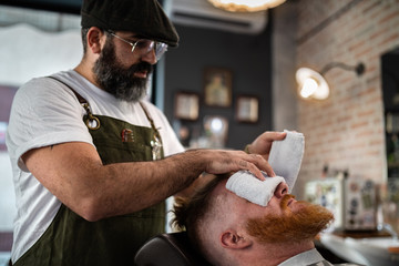 Barber doing face massage to handsome redhead man with closed eyes sitting in chair with warm hot towel covering face