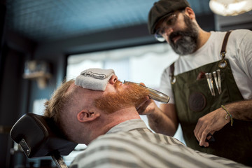 Barber with comb and trimmer cutting redhead man beard with towel covering eyes sitting in barbershop