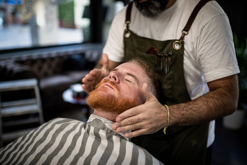 Cropped unrecognizable barber doing face massage to handsome redhead man with closed eyes sitting in chair