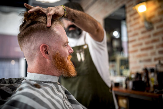Side view modern hairdresser barber cutting a adult man redhead's hair in barber chair
