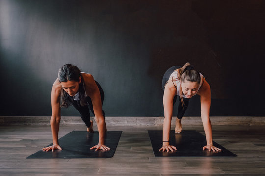 Barefoot women in sportswear concentrating and doing plank exercise on sports mats on wooden floor against white walls of spacious hall