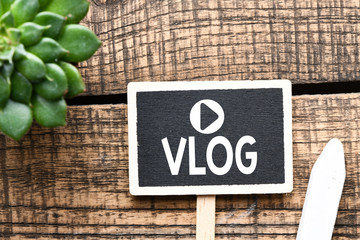 VLOG text concept. Vlog text on a small chalk board and wooden table.