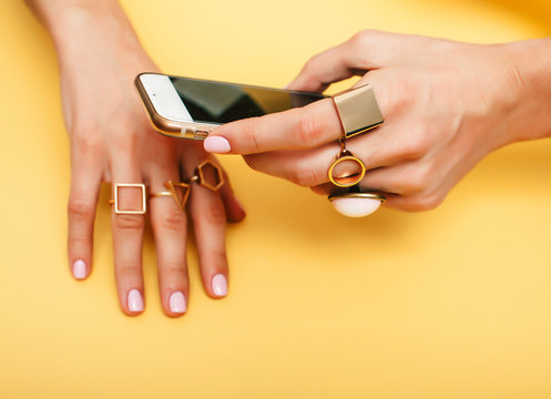 womans hand taking picture of her new manicure with fashion jewellery on her phone, girls stuff concept closeup