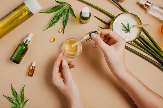 Pipette with CBD cosmetic oil in female hands on a table background with cosmetics, cream with cannabis and hemp leaves, marijuana