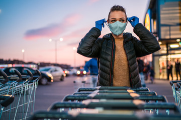 A woman wears medical protective gloves and a mask while shopping groceries.