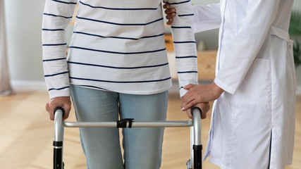 Fotomurales - Close up of supportive woman doctor give help assist disabled old lady holding walking frame, female nurse or caregiver support ill senior grandmother step with walker, rehabilitation concept