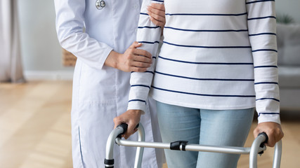Fotomurales - Female doctor support sick disabled old lady with walker at home or clinic, caring young woman nurse or caregiver give help to senior patient with walking frame, rehabilitation, physiotherapy concept