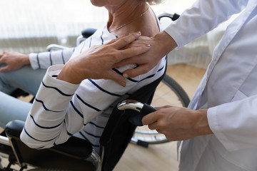 Fototapete - Close up of supportive nurse comfort hold hand of upset lonely handicapped old lady patient sitting in wheelchair, female caregiver or doctor take care of distressed disabled senior grandmother