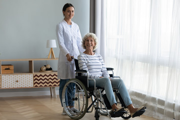 Fototapete - Portrait of young female nurse or caregiver posing give help to disabled happy old lady sitting in wheelchair, woman doctor assist support handicapped optimistic positive senior patient