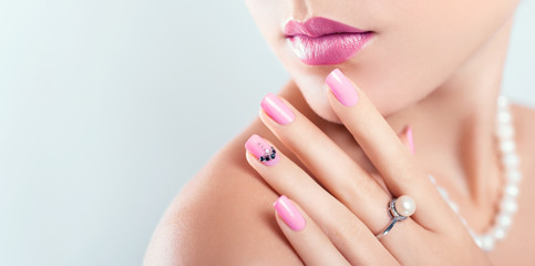 Fototapeten Maniküre Nail art and design. Beautiful woman wearing make-up and pearl jewellery showing pink manicure with gems. Banner