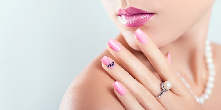 Nail art and design. Beautiful woman wearing make-up and pearl jewellery showing pink manicure with gems. Banner