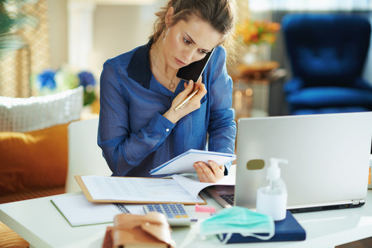 concerned trendy woman talking on phone and working