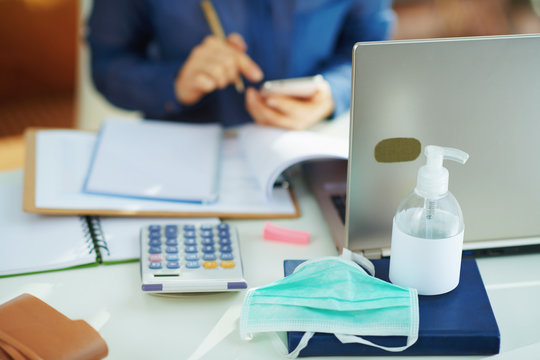 medical mask and hand disinfectant and woman working