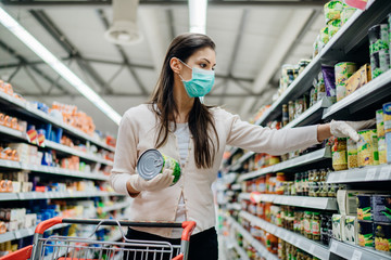 Autocollant pour porte Magasin alimentation Woman preparing for pathogen virus pandemic spread quarantine.Choosing nonperishable food essentials.Budget buying at a supply store.Pandemic quarantine preparation.Emergency to buy list