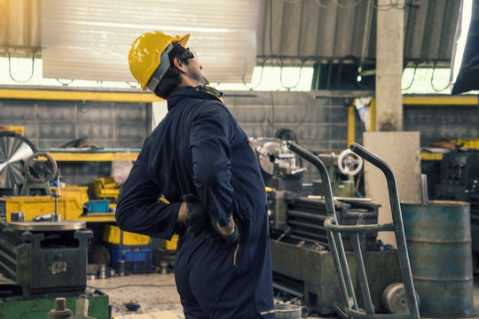 Mechanic engineers work hard, transport equipment, feel back pain while working in the factory.