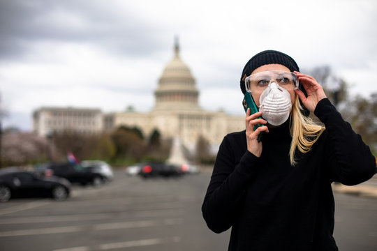 A woman protects herself from coronavirus while standing in front of the US Capitol building