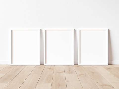 Vertical wooden frame poster on wooden floor with white wall. Wooden frame mock up. 3D illustrations.