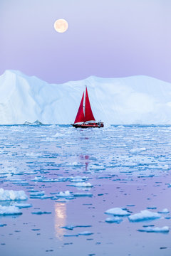 Sail boat with red sails cruising among ice bergs after sunset in front of the full moon rising. Disko Bay, Greenland.