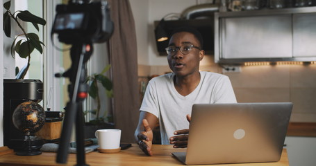 Happy young smart black blogger man filming new vlog video with professional camera in kitchen at home slow motion. Fotobehang