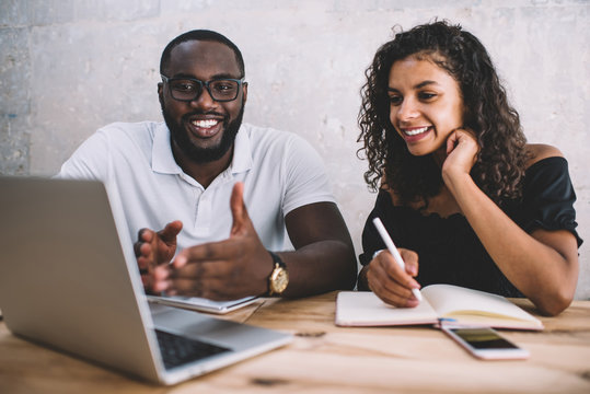 Cheerful african american male and female colleagues discussing project ideas making research on laptop computer, smiling dark skinned man explaining information to female student via webinar