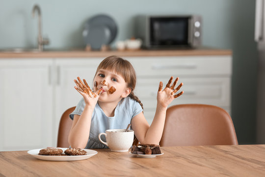 Cute little girl eating chocolate in kitchen
