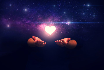 Spiritual image: hands with shining heart shape and spaceship ,Love from universe and love from gods concept.