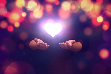 Spiritual image: hands with shining heart shape ,Love to all people and love from gods concept.