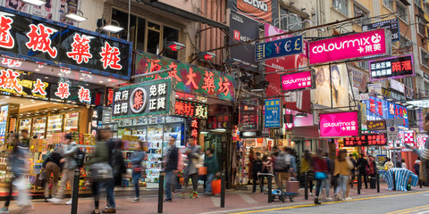 Hong Kong - December 9, 2018: Drugstore and pharmacy neon signs and blurred people walking in Lockhart Road, Causeway Bay, Hong Kong.