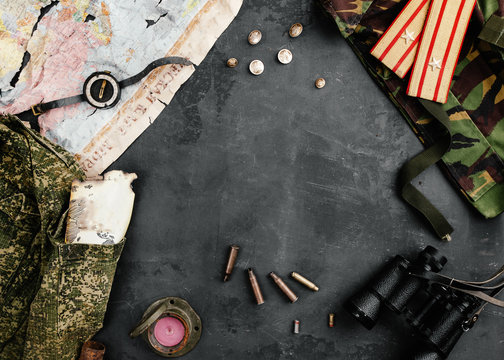 Military attributes and an old map lie on a black concrete background