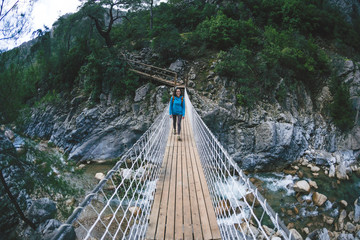 A girl with a backpack crosses the canyon on a suspension bridge.