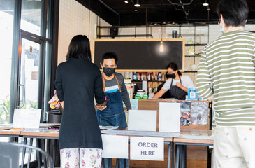 Social distance conceptual small business waiter serving customer at cafe.